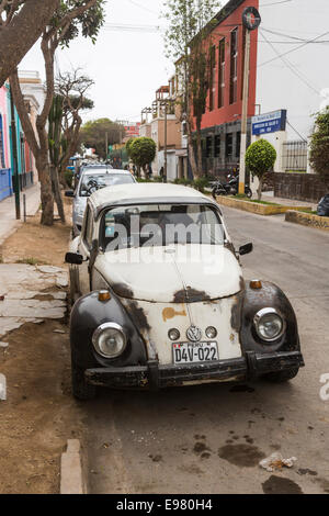 Dilapidated black and white Volkswagen Beetle car in a street in Barranco, Lima, Peru - Stock Photo