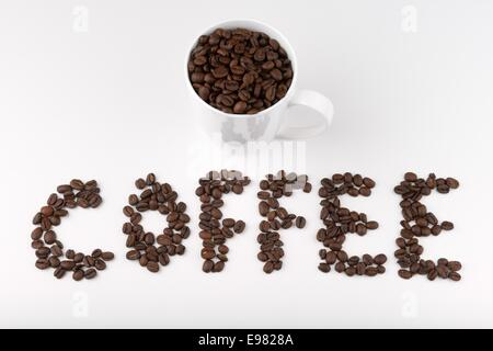 Coffee beans spelling out the word coffee and full cup - Stock Photo