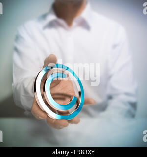 Man holding metallic copyright symbol. Concept image for illustration of author protection or intellectual property