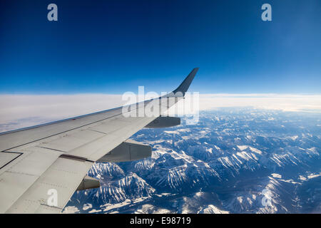 aerial view, the wing of the airplane visible out the window, clear blue sky and of the Rocky Mountains from an - Stock Photo