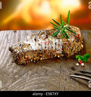 Rustic steak on wooden board in front of the fire - Stock Photo