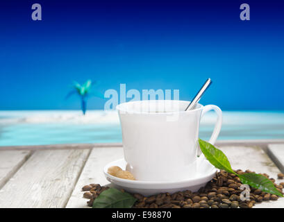 Freshly brewed cup of coffee with coffee beans on a wooden deck overlooking the tropical ocean - Stock Photo