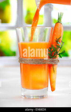 Pouring fresh carrot juice from a jug into a glass with a raw whole carrot strapped to the side with string - Stock Photo