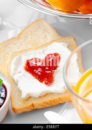 Strawberry jam in the shape of a heart on thick whipped cream topping a slice of fresh white bread - Stock Photo