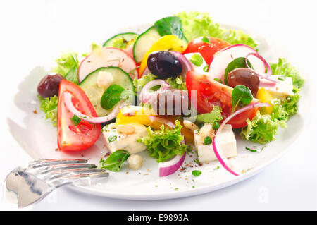 Healthy Greek salad served for lunch with crisp leafy greens, olives, feta, onion , tomato, cucumber and radish - Stock Photo