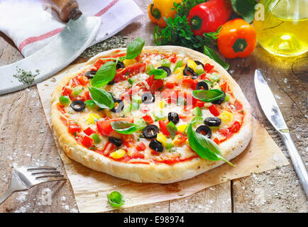 Freshly cooked vegetarian pizza served on oven paper in the kitchen surrounded by various ingredients used in the - Stock Photo