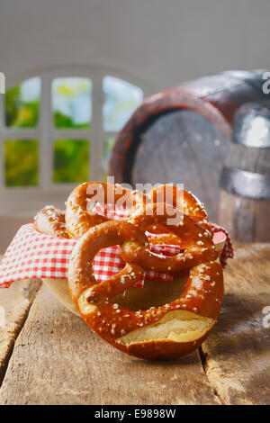 Crisp golden knot-shaped pretzels on a wooden table with an old vintage oak barrel and summery window behind - Stock Photo