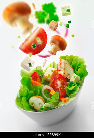 Individual side bowl of healthy fresh mixed green salad of lettuce, carrot, onion, mushrooms, tomato and feta with - Stock Photo