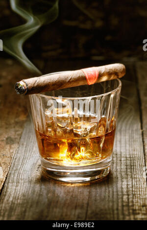 Burning Cuban cigar resting on glass of whisky on ice on an old wooden surface symbolic of masculinity - Stock Photo