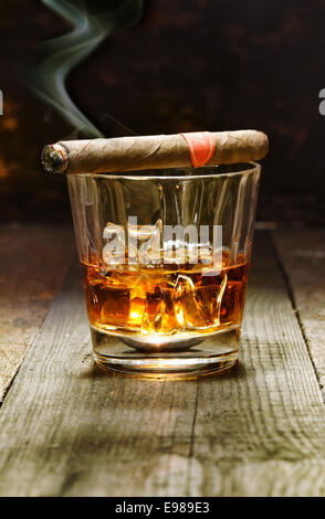 Burning Cuban cigar resting on a glass of brandy in a bar, the luxury pleasures of a wealthy macho man - Stock Photo