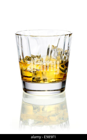 Glass of golden whiskey or brandy served on ice on a reflective white surface - Stock Photo