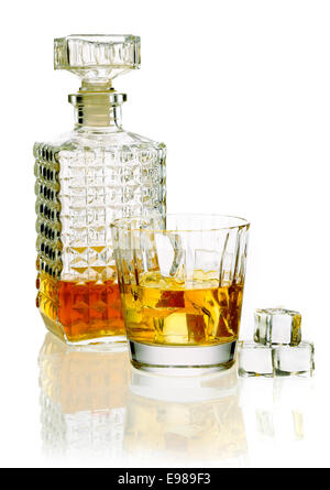 Whiskey or brandy decanter with a glass of whiskey on a reflective white surface - Stock Photo