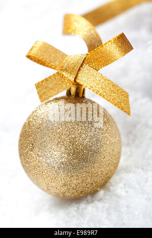 Closeup of a shiny gold glitter Christmas bauble with a decorative golden ribbon and bow on snow - Stock Photo