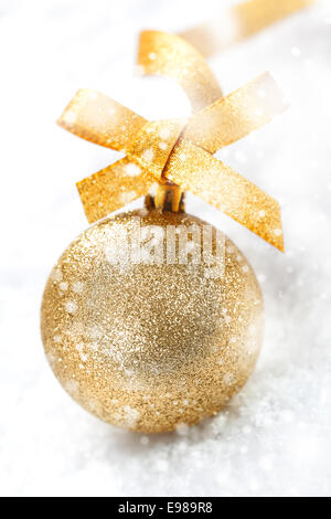 Glittering gold Christmas ball with an ornamental gold bow in winter snow with falling snowflakes - Stock Photo