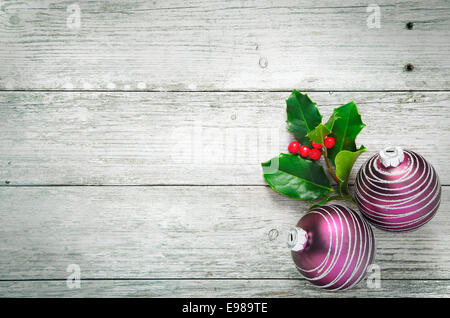 Christmas holly and pretty purple baubles with a spiral pattern on rustic wooden white painted boards with woodgrain - Stock Photo