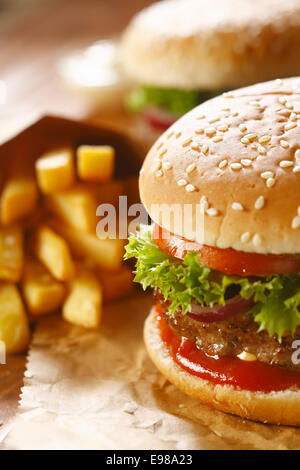 Two hamburgers and french fries with sesame bun on brown paper. selective focus - Stock Photo