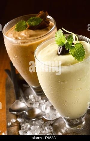 Closeup high angle view of two ice cold creamy double thick puddings or yoghurt dessert served in tall glasses garnished - Stock Photo