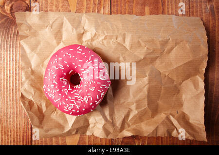 Overhead view of a pink strawberry doughnut with sprinkles on a sheet of crumpled grungy brown paper with copyspace - Stock Photo