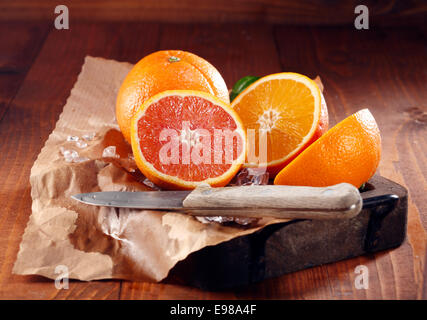 Juicy oranges, one whole and some sliced in halves on brown paper with knife - Stock Photo