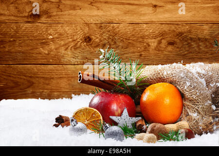Artistic Christmas still life of colourful fruit and spices spilling out of a rustic burlap bag onto winter snow - Stock Photo