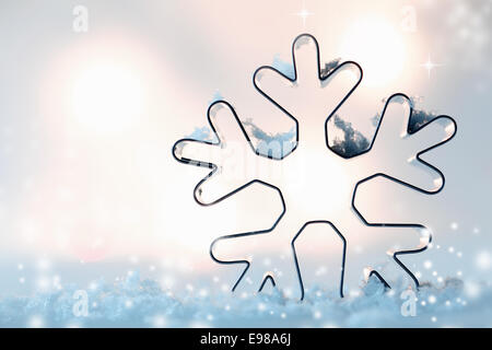 Outline of a snowflake cookie cutter in sparkling snow with soft muted lights in the background with copyspace for - Stock Photo