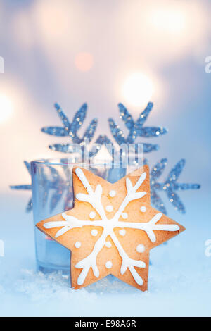 Crisp golden star snowflake cookie with decorative icing backed by an ornamental snowflake against soft ethereal - Stock Photo
