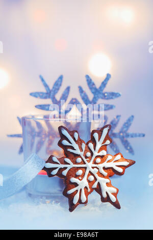 Decorative iced gingerbread Christmas snowflake biscuit with a snowflake ornament against a soft bokeh of party - Stock Photo