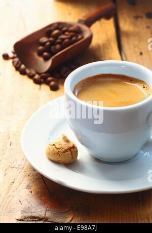 Strong aromatic espresso coffee served in a small cup with a macaroon on the side and a scoop of coffee beans in - Stock Photo