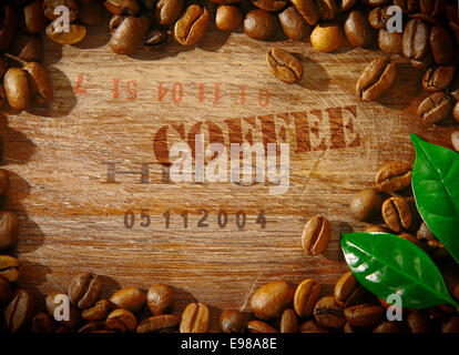 Fresh roasted coffee beans framing an old wooden board stamped with the word COFFEE and the shipment number of a - Stock Photo