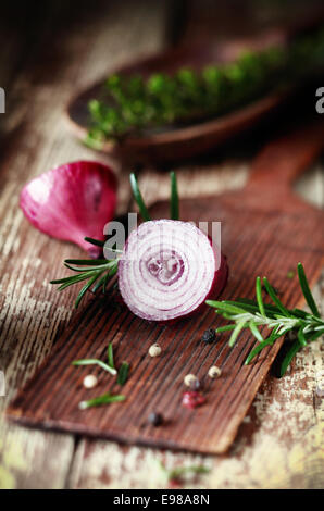 Sliced half red onion and herbs on a rustic wooden chopping board in a country kitchen during preparation as ingredients - Stock Photo