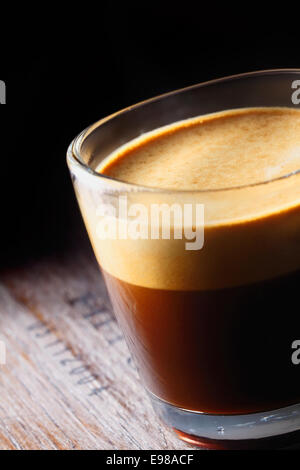 Cropped closeup of a frothy aromatic mug of fresh coffee in a glass mug on an old wooden table with shadowed background - Stock Photo