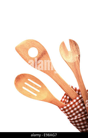 Three traditional rustic kitchen utensils in a red and white checkered cloth, isolated on white background - Stock Photo