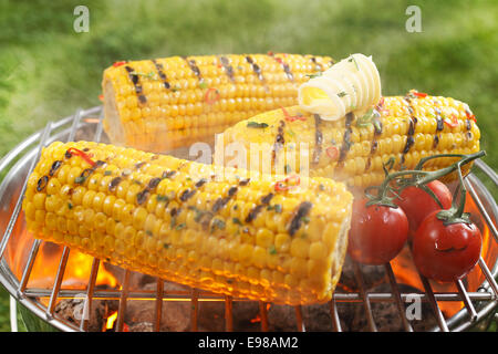 Healthy vegetarian barbecue with ripe golden corn on the cob and juicy red cherry tomatoes grilling over the fire - Stock Photo
