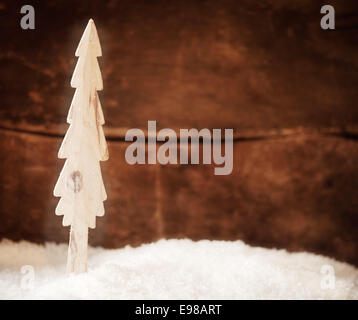 Stylised wooden Christmas tree standing in fresh winter snow in front of a rustic timber wall with copyspace for - Stock Photo