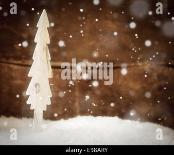 Pretty Christmas card background with a simple wooden Christmas tree standing in snow during a snowfall against - Stock Photo