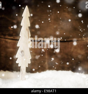 Falling snowflakes on a small stylised wooden Christmas tree standing in a bed of snow in front of a wooden wall - Stock Photo