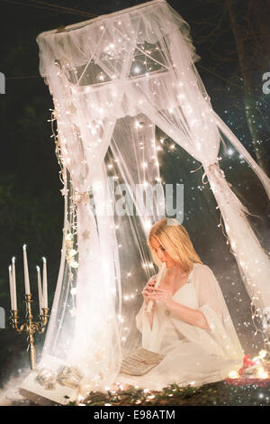 Beautiful Christmas angel in a forest sitting under a white lace canopy surrounded by stars, glowing candles and - Stock Photo