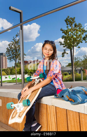 Beautiful girl holds skateboard and sits on side - Stock Photo