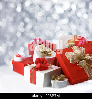 Collection of festive decorative Christmas gifts in red, white and gold lying in winter snow against a bokeh of - Stock Photo