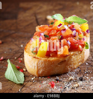 Cooking colourful bruschetta with toasted crispy sliced baguette topped with chopped tomato, onion, oil, seasoning - Stock Photo