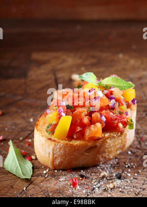 Tomato bruschetta or antipasti with a finely chopeed tomato and onion mixed with oil on a slice of crisp crusty - Stock Photo