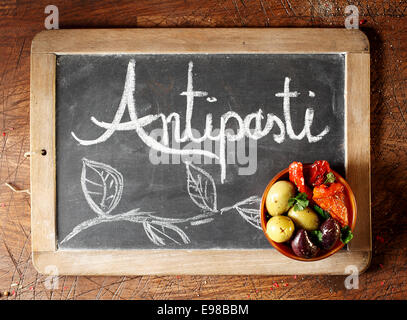 Chalkboard Antipasti sign with handwritten text and decorative foliage with a small bowl of black and green olives - Stock Photo