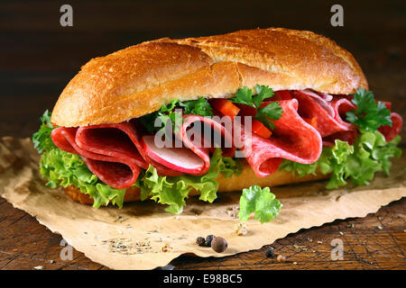 Freshly baked golden crusty baguette filled with fresh lettuce and thinly sliced salami seasoned with spices on - Stock Photo