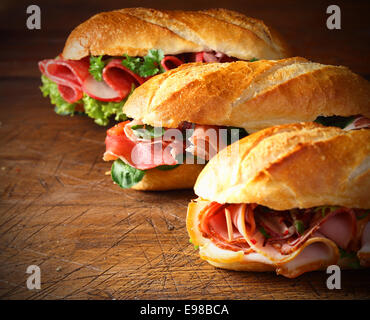 Assorted delicious baguette sandwiches filled with thinly sliced ham or salami and fresh green lettuce or basil - Stock Photo