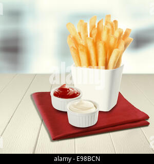 Crisp fried potato batons or chips standing upright in a white ceramic container with a side serving of tomato ketchup - Stock Photo