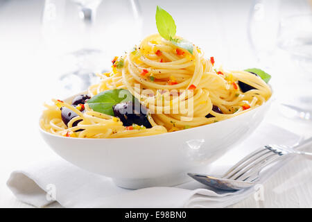 Close up shot of spaghetti pasta in a white bowl with olives on a white napkin with wine glasses in the background. - Stock Photo