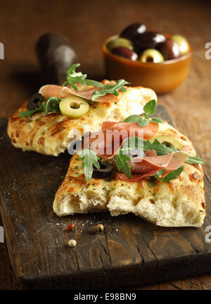 Delicous traditional oven-baked Italian focaccia bread topped with ham, rocket and olives on old cracked wooden - Stock Photo