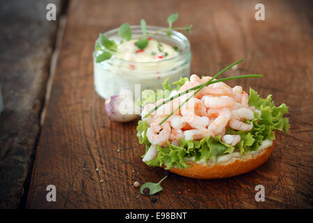 Gourmet shrimp bruschetta, an Italian antipasti, on a bed of fresh green lettuce on toasted baguette served with - Stock Photo