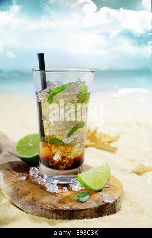 Refreshing iced rum cocktail served in a tall glass on a wooden board with sliced lemon on the golden sand of an - Stock Photo