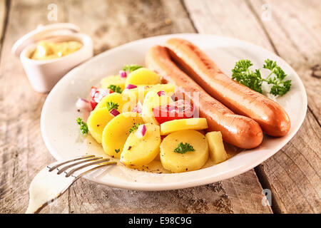 Two grilled Wiener sausages with baby potatoes, herbs and tomato on a white plate on a rustic wooden surface - Stock Photo
